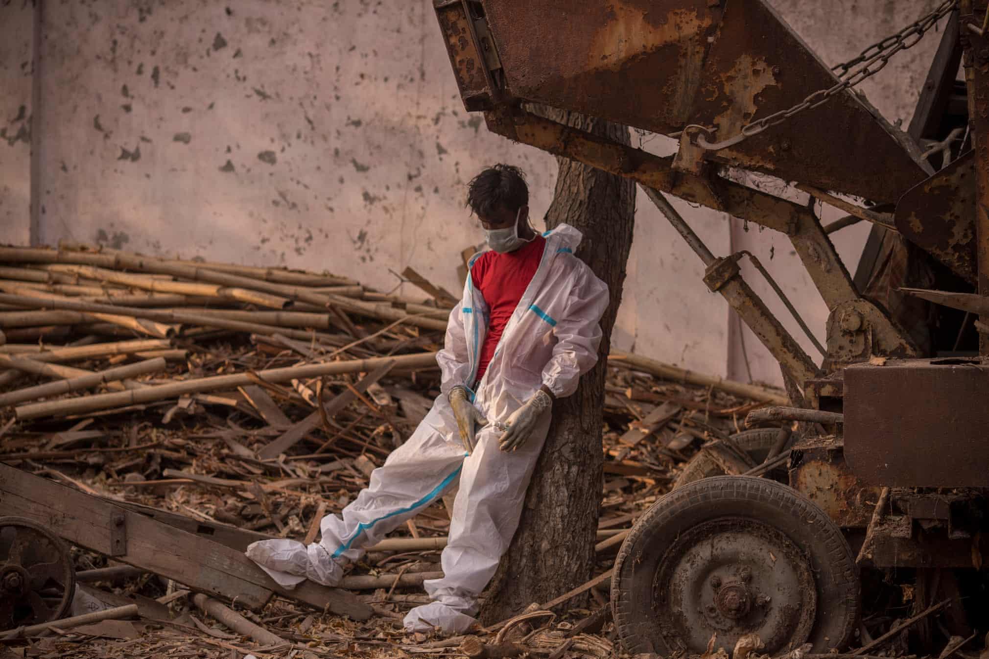 کارگر خسته و بی رمق هندی در محل سوزاندن اجساد کرونایی + عکس