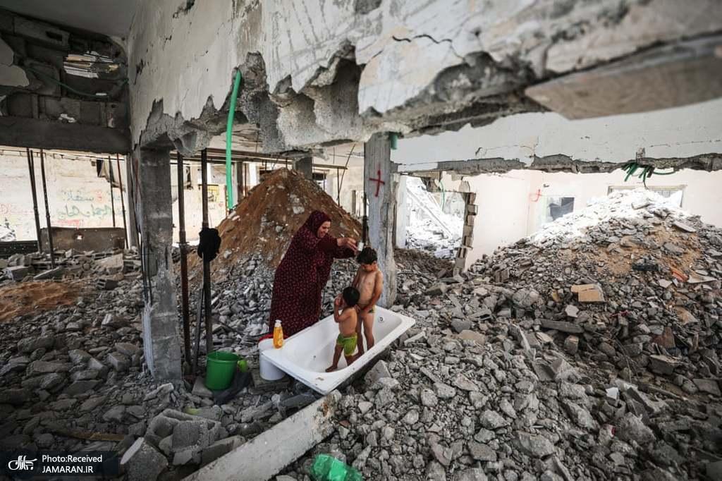 حمام کردن دو کودک فلسطینی در میان آوارها + عکس