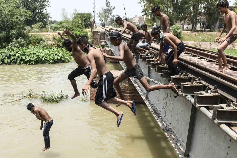 پرش نوجوانان هندی در آب در یک روز داغ + عکس