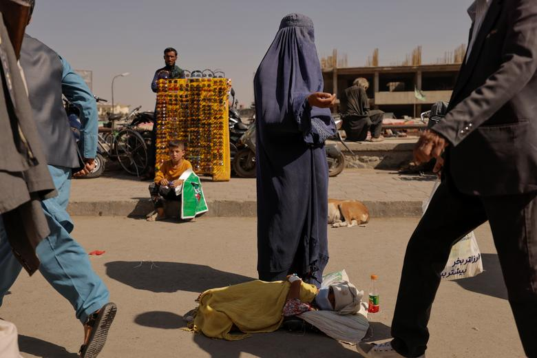 نیازمندی زن برقع پوش افغان و کودکش در کنار خیابان