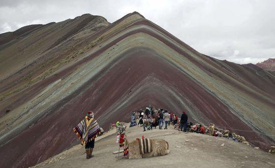ساکنین محلی آند بالاما و توریست ها در مقابل کوه وینیکونکا در پرو