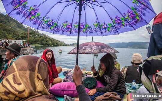 اندونزی خانواده هایی که منتظر گروه های امدادی هستند تا مفقودین حادثه غرق شدن قایق ۱۸۰ نفره در دریاچه گردشگری توبا را پیدا کنند. شمال سوماترا