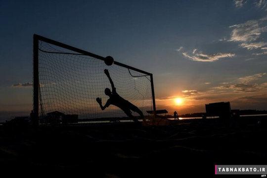 روسیه: پسری که در هنگام غروب در ساحل رود وولگا در حال بازی فوتبال است