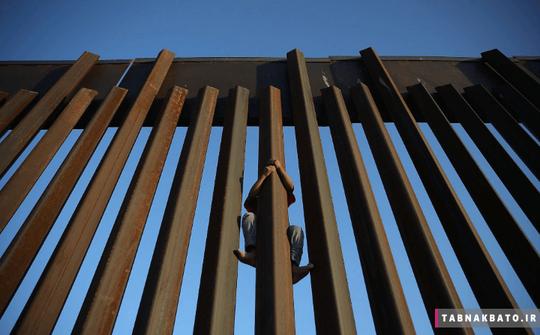 مکزیک: کودک مکزیکی که سعی دارد از نرده های مرزی بین آمریکا و مکزیک عبور کند