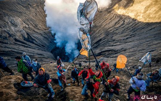 اندونزی: تعدادی از مردم در حال گرفتن اشيایی هستند که افراد قبیله تِنگه براساس آداب و رسوم  در دهانه آتشفشان برومو پرتاب می کنند