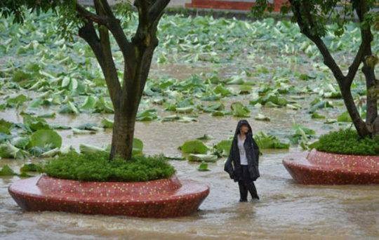یک پسر ایستاده در یک خیابان سیل زده در چنگدوی چین