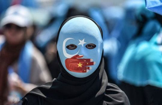 یک تظاهرکننده با ماسک منقش به پرچم شرق ترکستان و چین در اعتراض به کشتار اویغورها