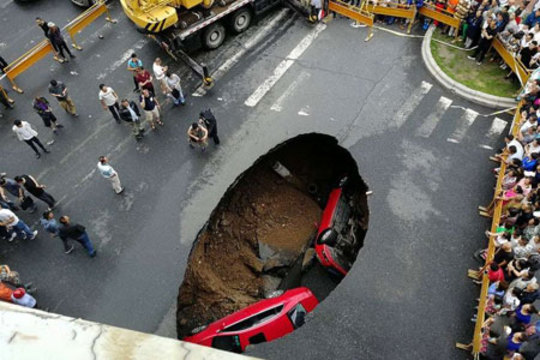 سقوط دو خودرو به یک گودال ایجاد شده در خیابانی در هاربین چین