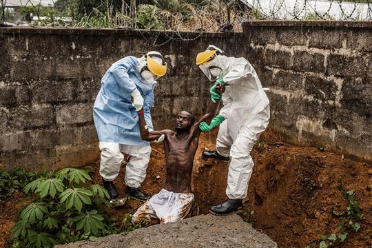 در سیرالئون در مرکز نگهداری از بیماران دچار ابولا، این مرد دچار توهم و جنون ناشی از بیماری شده و سعی کرده است که فرار کند. این بیمار، زمان کوتاهی بعد از گرفته شدن این عکس، درگذشت.