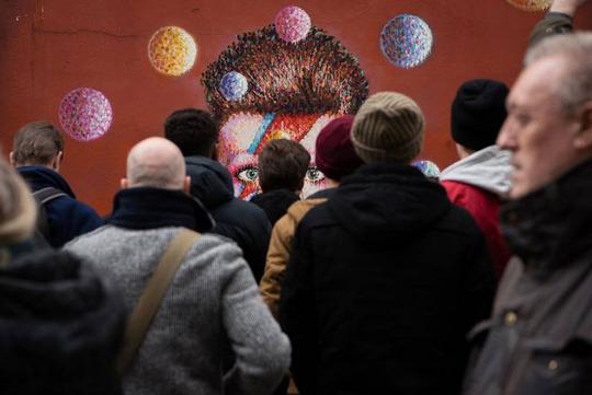 مردم در سوگواری دیوید بویی -خواننده درگذشته- شرکت کردهاند و به نقاشی او مینگرند.