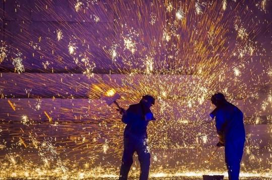 چین، کارگران در حال پخش گداخته های آهن داغ، برای جذب گردشگر،  استان هه بی