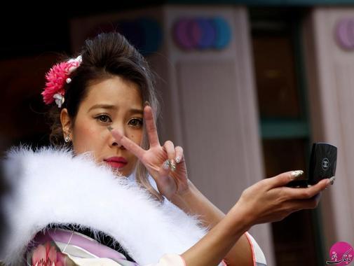 چهره یک دختر ژاپنی که در حین بررسی آرایش خود با انگشتانش علامت V (موفقیت) را به دوربین نشان می دهد. مکان: توکیو – ژاپن؛ عکاس: Kim Kyung Hoon