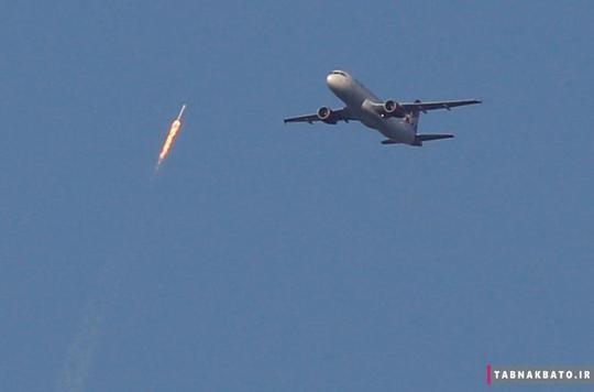 اوج گرفتن موشک فالکون 9 شرکت اسپیسکس بر فراز هواپیمای خطوط هوایی ویرجین که لحظاتی قبل، فرودگاه بین المللی اورلاندو را ترک کرده بود.