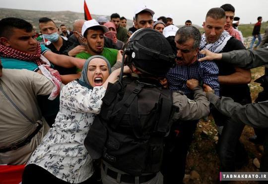 تلاش فلسطینیان برای جلوگیری از بازداشت یک معترض توسط نظامیان رژیم صهیونیستی در حرکت اعتراضی در روز زمین در کرانه باختری.