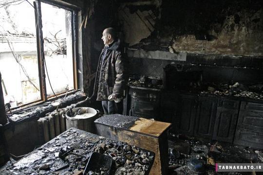 یک ساکن محلی در شهر دونتسک اوکراین به بیرون خیره شده است و خانهی گلوله باران شدهی خود را نظاره میکند.