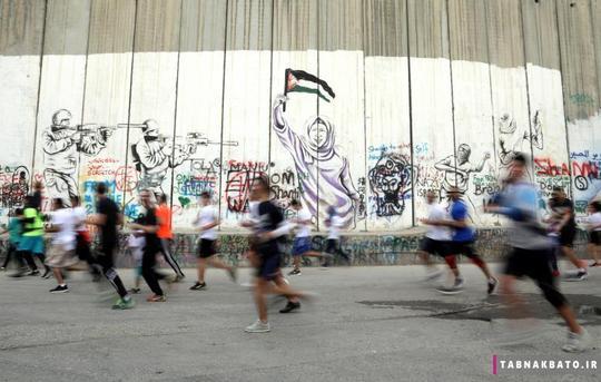 عبور شرکت کنندگان دو ماراتون از کنار دیوار حائل رژیم صهیونیستی در زمان برگزاری دو ماراتون سالانه فلسطین در شهر بیت لحم در کرانه باختری.