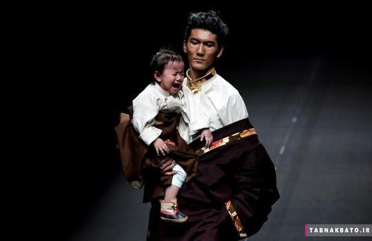 واکنش یک دختر بچه در آغوش یک مدل لباس در لحظهی نمایش لباسهای طراح تبتی به نام «ای.جی نامو» در یک فشن شو در هفته مد چین در شهر پکن.
