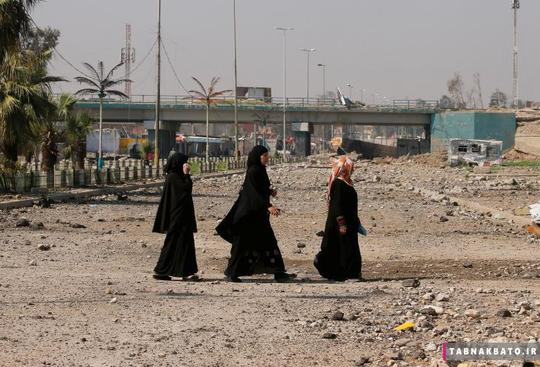 زنان عراقی در حال عبور از خیابانی در منطقه تحت کنترل نیروهای عراقی در غرب موصل.