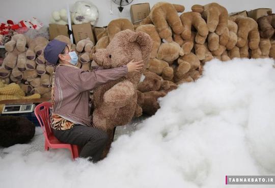 کارگری در حال پر کردن پنبه در عروسکهای خرسی در کارخانهی تولید اسباببازی شهر ووهان استان هوبی