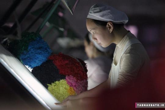 یک زن در حال کار در یک کارخانه نساجی در ژیانگفان در استان هوبی چین