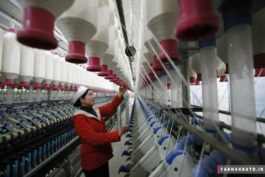 کارگری در حال کار در کارخانهی ریسندگی و بافندگی در هوایبی استان آنهوی چین