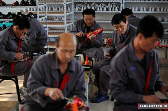 کارگران اهل کشور کره شمالی در حال تولید کفش ورزشی در یک کارخانهی موقت در روستایی در اطراف شهر داندونگ
