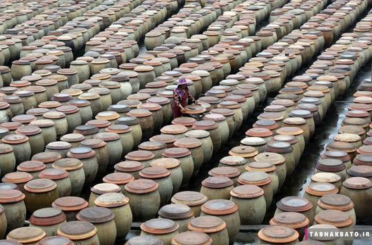 یک زن در حال کار در یک کارخانهی تولید سنتی سُس سویا در شهر جینجیانگ استان فوجیان چین