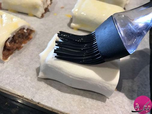 مخلوط شیر و تخم مرغ را با قلمو یا چنگال، روی لقمههای گوشتی میمالیم