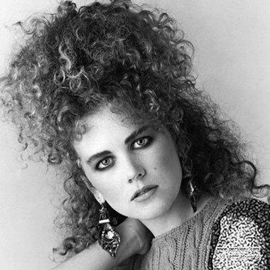 1987 ستاره تلویزیونی استرالیایی موهای فر طبیعی خود را به شکل یک دم اسبی در بالای سرش بسته و از یک خط چشم نمایشی استفاده کرده است.