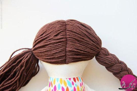 موهای عروسک را نیز در وسط سر آن قرار داده و گیسباف میکنیم